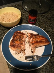 Salmon, cooked, next to brown rice and red curry paste